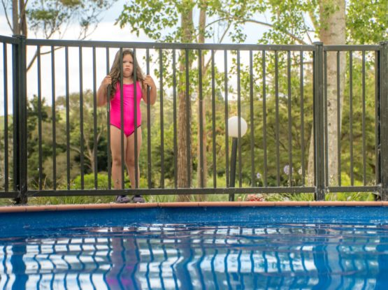 Metal pool fencing in Leppington, NSW with girl standing outside for safety