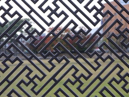 Straight image of a patterned steel fence.