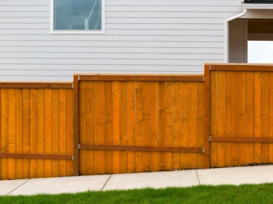 New home backyard red stained cedar wood fence construction